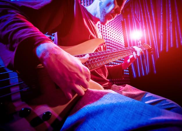 Młody człowiek bawić się na gitarze basowej w rozsądnym studiu nagrań.