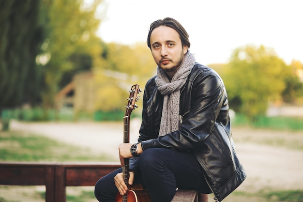 Młody człowiek bawić się na gitarze przy jeziorem