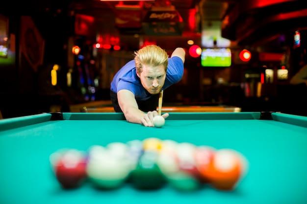 Młody człowiek bawić się snooker w barze