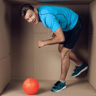Młody człowiek bawić się z piłką w kartonie.