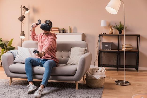 Młody człowiek bawić się z wirtualnym zestawem słuchawkowym
