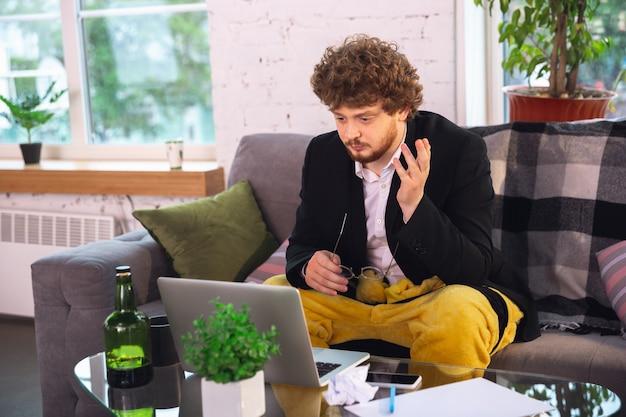 Młody człowiek bez spodni, ale w kurtce pracujący na komputerze, laptopie.