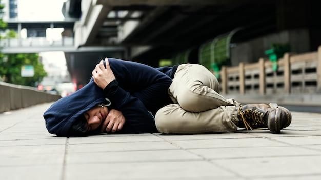 Młody człowiek bezdomny spać na ulicy