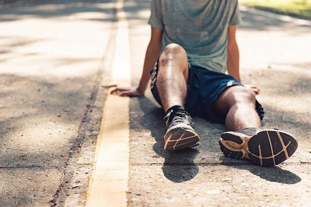 Młody człowiek biegacz odpoczywa po treningu na pogodnym ranku.