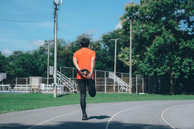 Młody człowiek biegacz rozciągania nóg. koncepcja aktywnego i zdrowego stylu życia.