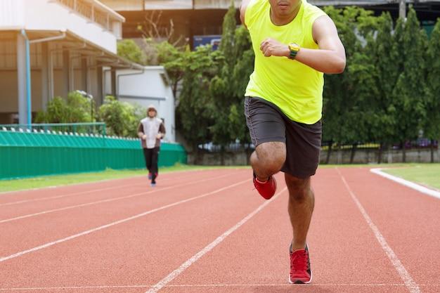 Młody człowiek biegający w słoneczny poranek na torze stadionowym