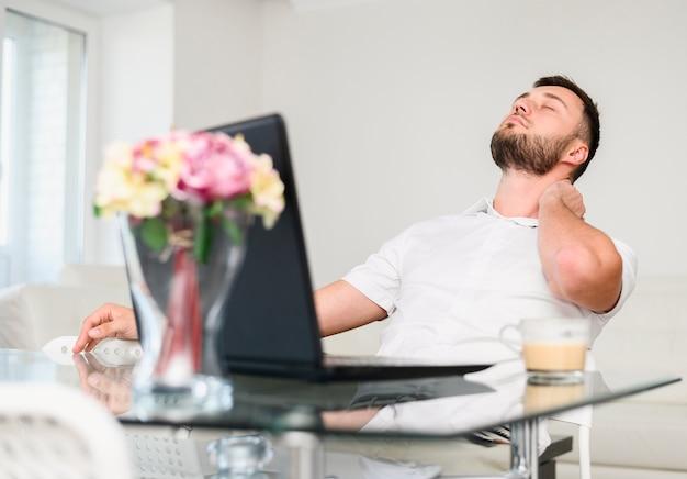 Młody człowiek bierze przerwę dla relaksu przy biurem