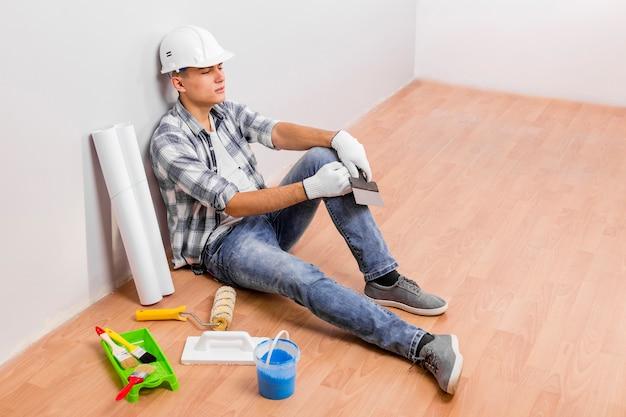 Młody człowiek bierze przerwę podczas gdy siedzący na podłoga