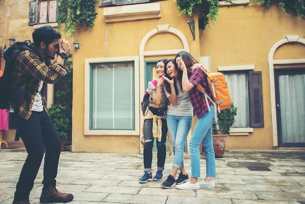 Młody człowiek bierze selfie jego przyjaciele podczas gdy podróżujący w miastowym wpólnie.