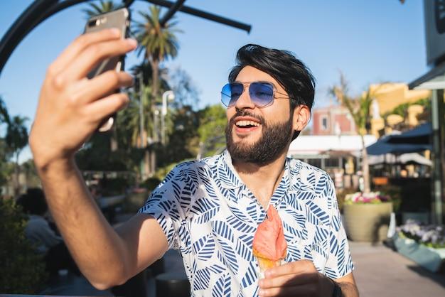 Młody człowiek bierze selfie podczas gdy jedzący lody.