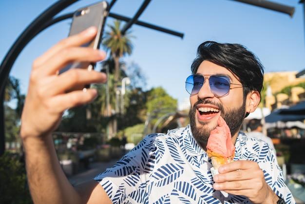 Młody człowiek bierze selfie podczas gdy jedzący lody