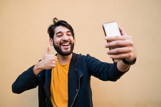 Młody człowiek bierze selfie z telefonem.
