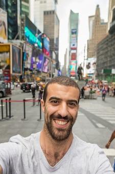 Młody człowiek biorąc selfie na times square
