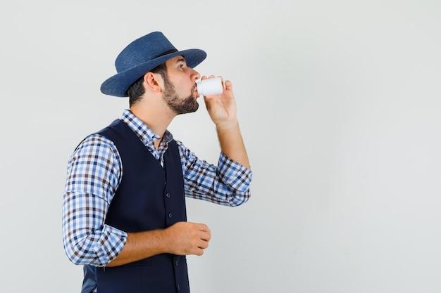 Młody człowiek biorąc tabletki w koszuli, kamizelce, kapeluszu