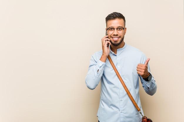 Młody człowiek biznesu azjatyckich rasy mieszanej trzymając telefon uśmiechnięty i podnoszący kciuk do góry