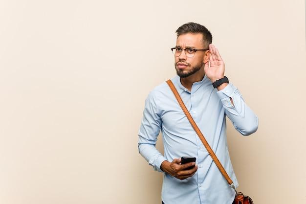 Młody człowiek biznesu azjatyckiej rasy mieszanej trzyma telefon próbuje wysłuchać plotek.