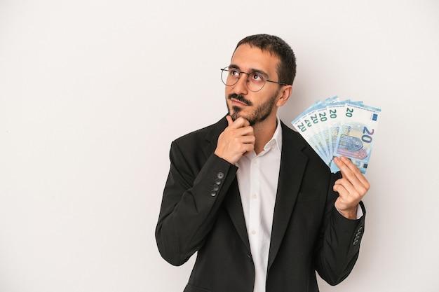 Młody człowiek biznesu kaukaski gospodarstwa banknotów na białym tle patrząc w bok z wyrazem wątpliwości i sceptyczny.