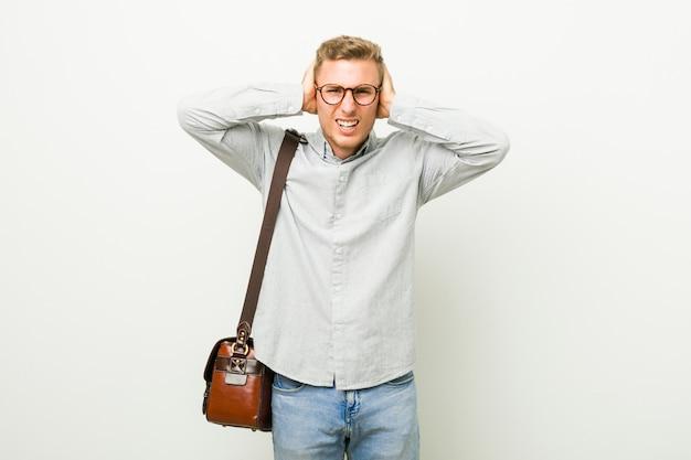 Młody człowiek biznesu kaukaski obejmujące uszy rękoma, starając się nie słyszeć zbyt głośnego dźwięku.