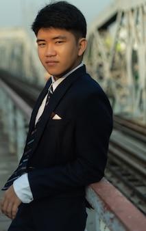 Młody człowiek biznesu pewność, opierając się na poręczy mostu