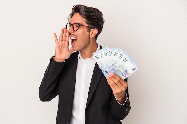 Młody człowiek biznesu rasy mieszanej gospodarstwa rachunki na białym tle krzycząc i trzymając dłoń w pobliżu otwarte usta.