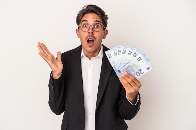 Młody człowiek biznesu rasy mieszanej gospodarstwa rachunki na białym tle zaskoczony i zszokowany.