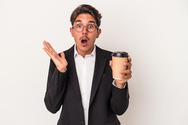 Młody człowiek biznesu rasy mieszanej gospodarstwa zabrać kawę na białym tle zaskoczony i zszokowany.