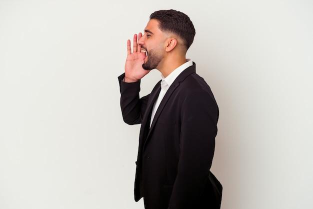 Młody człowiek biznesu rasy mieszanej na białym tle krzycząc i trzymając dłoń w pobliżu otwartych ust.