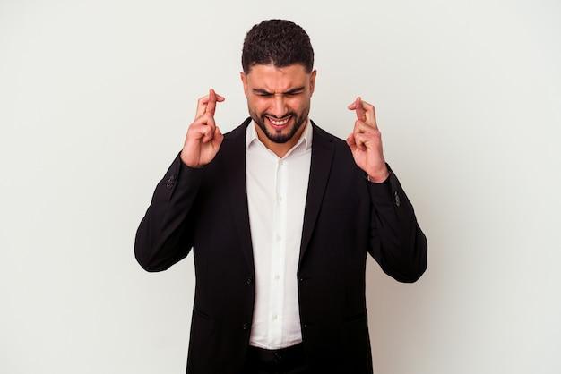 Młody człowiek biznesu rasy mieszanej na białym tle na białej ścianie kciuki za szczęście