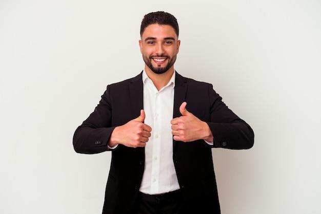 Młody człowiek biznesu rasy mieszanej na białym tle na białej ścianie z kciuki do góry, wiwaty o czymś, koncepcja wsparcia i szacunku.