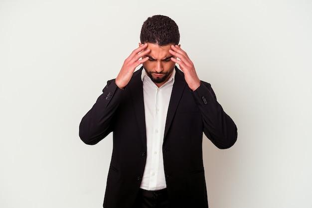 Młody człowiek biznesu rasy mieszanej na białym tle na białym tle dotykając świątyń i mając ból głowy.