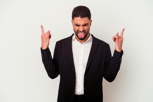 Młody człowiek biznesu rasy mieszanej na białym tle na białym tle wyświetlono rock gest palcami