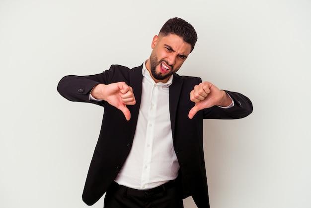 Młody człowiek biznesu rasy mieszanej na białym tle pokazując kciuk w dół i wyrażający niechęć.