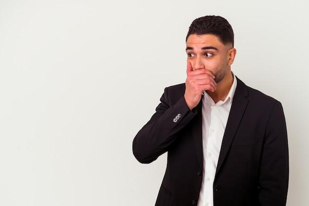 Młody człowiek biznesu rasy mieszanej na białym tle zamyślony patrząc na przestrzeń kopii obejmującej usta ręką.