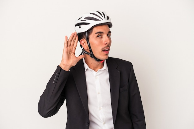 Młody człowiek biznesu rasy mieszanej sobie kask rowerowy na białym tle próbuje słuchać plotek.