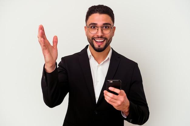 Młody człowiek biznesu rasy mieszanej trzymając telefon komórkowy mężczyzna na białym tle odbiera miłą niespodziankę, podekscytowany i podnosząc ręce.
