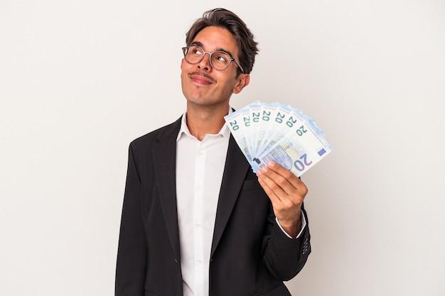Młody człowiek biznesu rasy mieszanej, trzymający rachunki na białym tle, marząc o osiągnięciu celów i celów