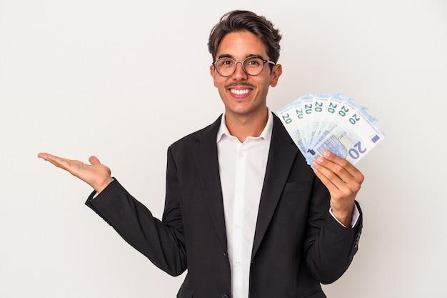 Młody człowiek biznesu rasy mieszanej trzymający rachunki na białym tle na białym tle pokazujące miejsce na kopię na dłoni i trzymający inną rękę na pasie.