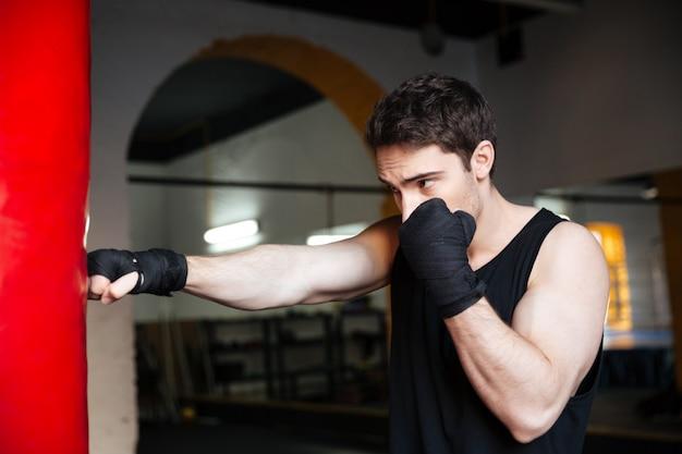 Młody człowiek bokser szkolenia z workiem bokserskim