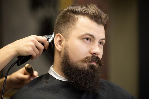 Młody człowiek brodaty w salon fryzjerski