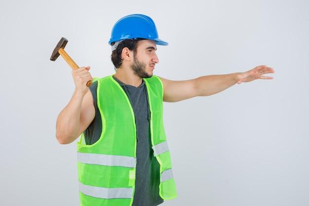 Młody człowiek budowniczy przygotowuje się do używania młotka w mundurze odzieży roboczej i wygląda pewnie, widok z przodu.