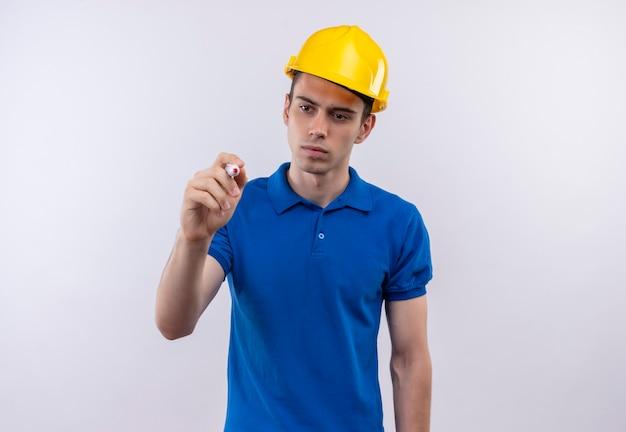 Młody człowiek budowniczy sobie mundur konstrukcyjny i kask pisze piórem