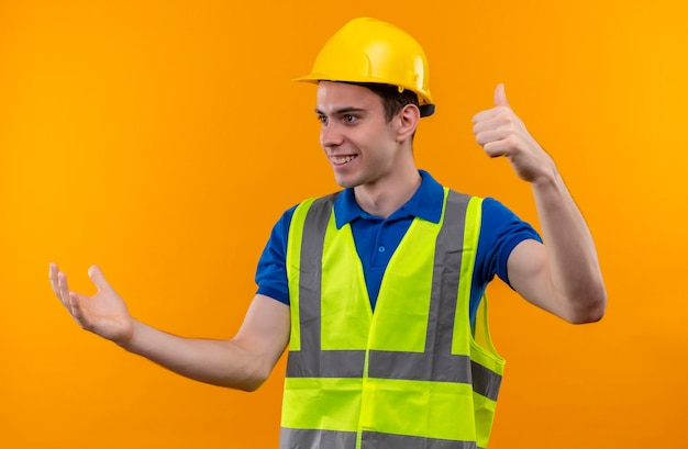 Młody człowiek budowniczy sobie mundur konstrukcyjny i kask robi szczęśliwe kciuki do góry