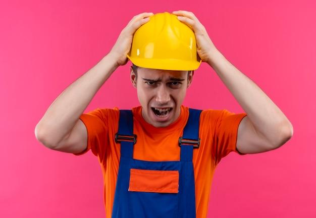 Młody człowiek budowniczy sobie mundur konstrukcyjny i kask, trzymając głowę rękami