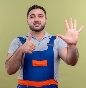 Młody człowiek budowniczy w mundurze budowy pokazując numer pięć i kciuki do góry uśmiechnięty z radosną buźkę