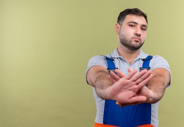 Młody człowiek budowniczy w mundurze budowy skrzyżowania broni, czyniąc gest obrony z poważną miną