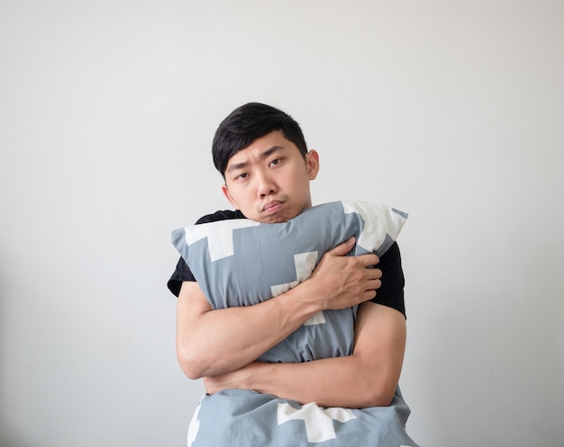 Młody człowiek budzi się i przytula poduszkę, patrzy na znudzoną twarz na białym odosobnionym tle