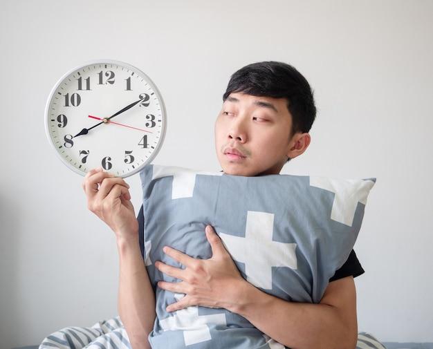 Młody człowiek budzi się przytulając poduszkę i patrzy na zegar w dłoni, czuje się znudzony twarzą na białym tle