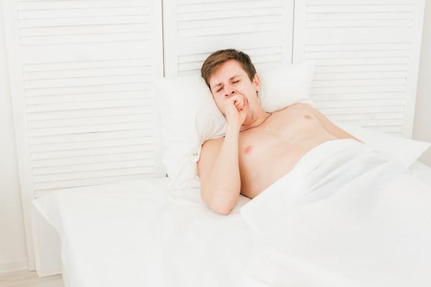 Młody człowiek budzi się rano