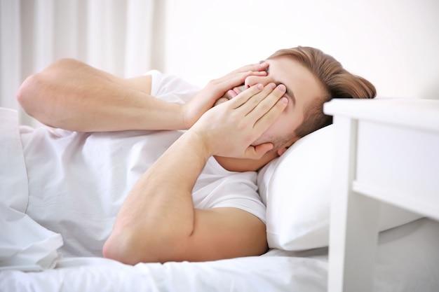 Młody człowiek budzi się w domu w łóżku