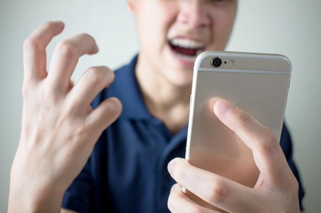 Młody człowiek był zły na smartfona z powodu problemów lub błędów.